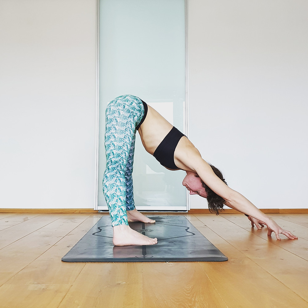 A woman doing a yoga pose, a forward fold