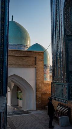 Man standing infront of the Shah-I-Zinda (mausoleum avenue), Samarkand, Uzbekistan