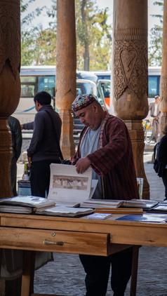 Man selling paintings outside Bolo Hauz Mosque, Bukhara, Uzbekistan