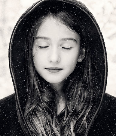 Beautiful girl in hood with eyes closed.