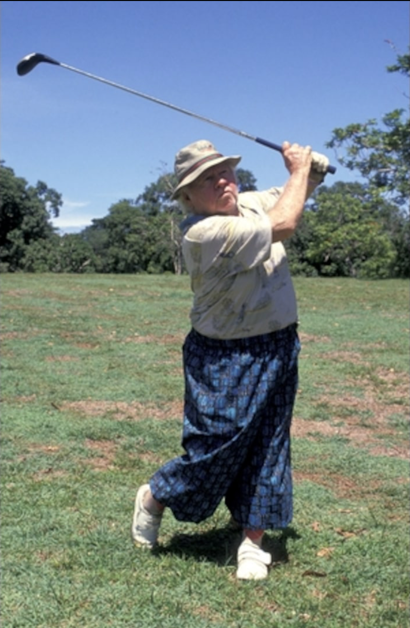 Mickey Rooney finishes his golf swing