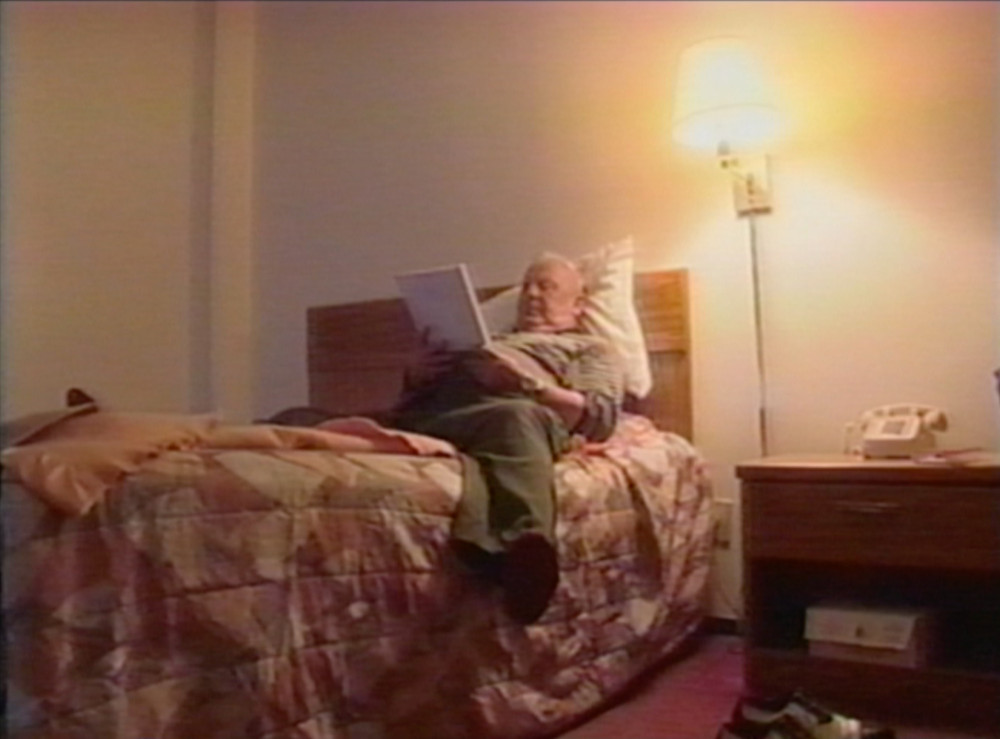 """Moe Norman lies in his Ontario motel room reading """"The Bertholy Method"""" golf book  (still image from """"Moe Norman: The King of Swing"""" (2002), directed by Anne Pick)"""