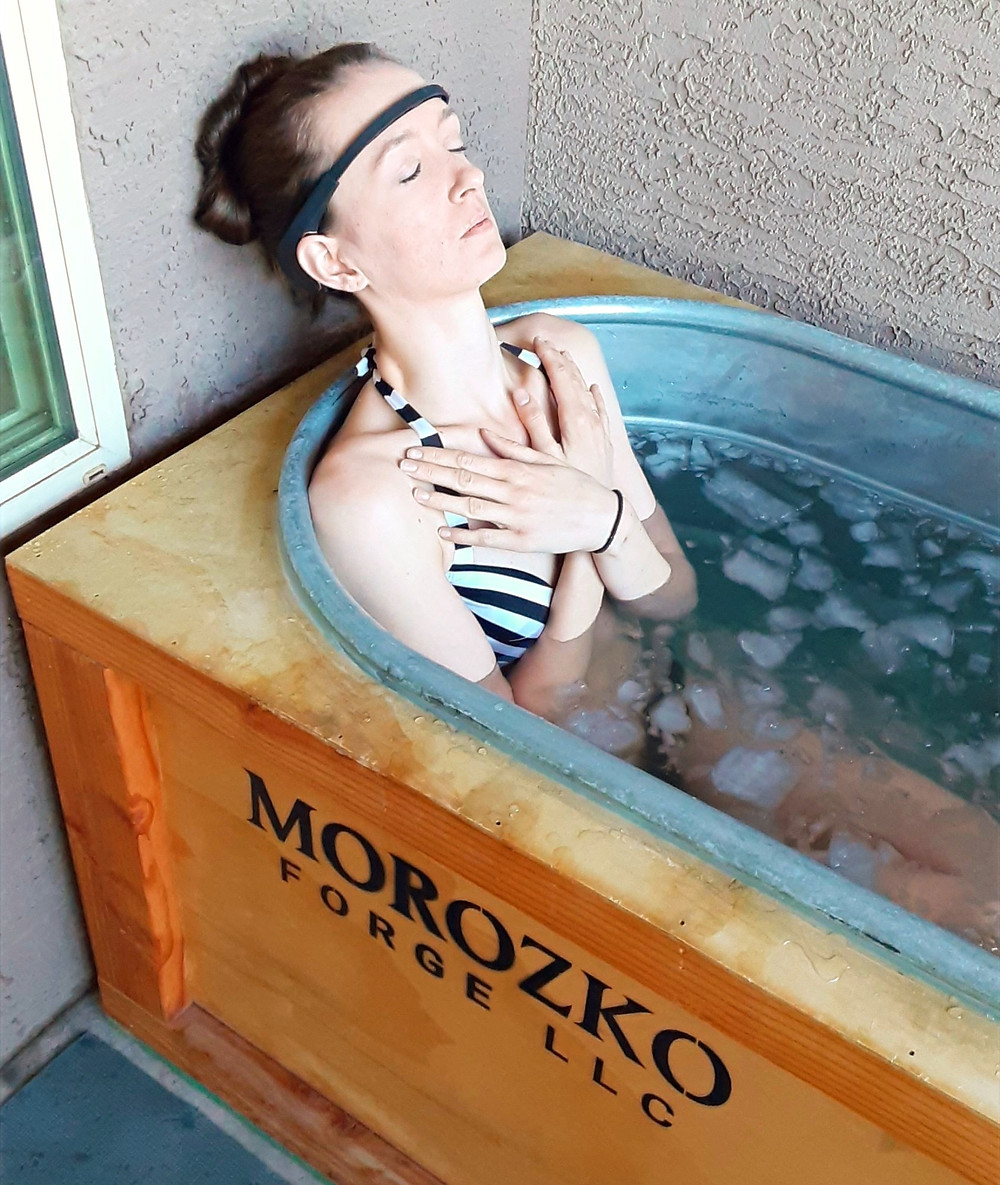 Woman relaxing in ice bath with eyes closed and hands crossed over her chest.