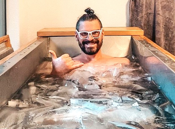 Bearded man with white-rimmed glasses is smiling while immersed up to his neck in ice water.