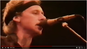 Singer Mark Knopfler performing 'Industrial Disease' with the band Dire Straits.