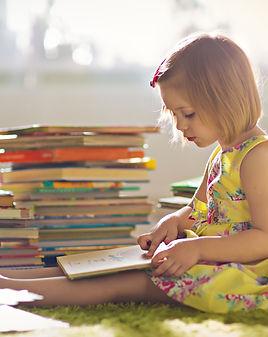 A little cute girl in a yellow dress rea