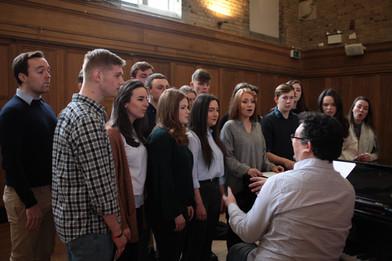 DE FAV choir at piano in MH REHEARSAL 4.