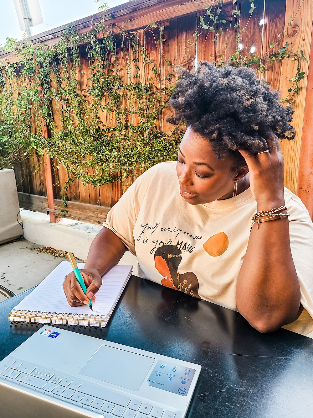 African American woman sitting outdoors at a table, writing on a spiral notebook with a teal colored pen in right hand, adn an open laptop in front. Left hand is bent up and fingers inside of her curly tapered haircut. Ivory colored shirt with an African American woman on the front, and illegible black writing. Wooden fence with green vines behind her. Shanell Tyus. Black Blogger.