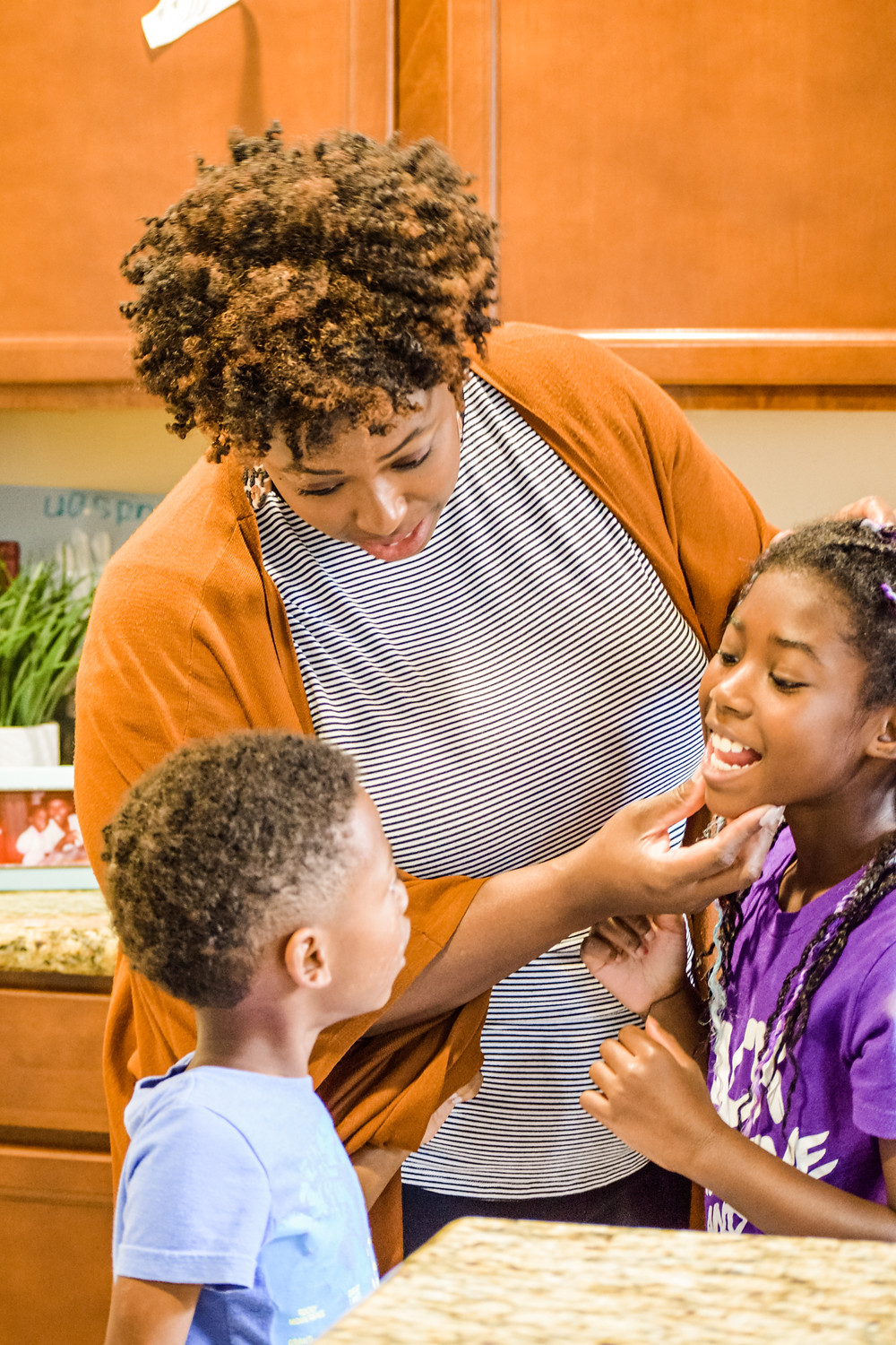 Shanell Tyus Black Mom in the kitchen with daughter and son. Natural curly hair kids, family in the kitchen. Black Mom and Black children.