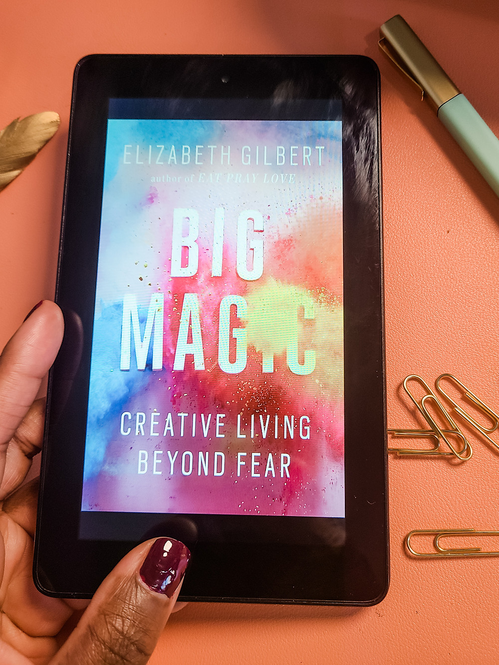 Black, Creative, and Dope. Working in home office. Shanell Tyus. Black xennial mom. Millennial mom. Naturalista. Curly-haired mom. Taperd cut. Cozy home office. Work from home mom. Mompreneur. Finding your passion. Black woman's hand holding digital copy of Big Magic by Elizabeth Gilbert.
