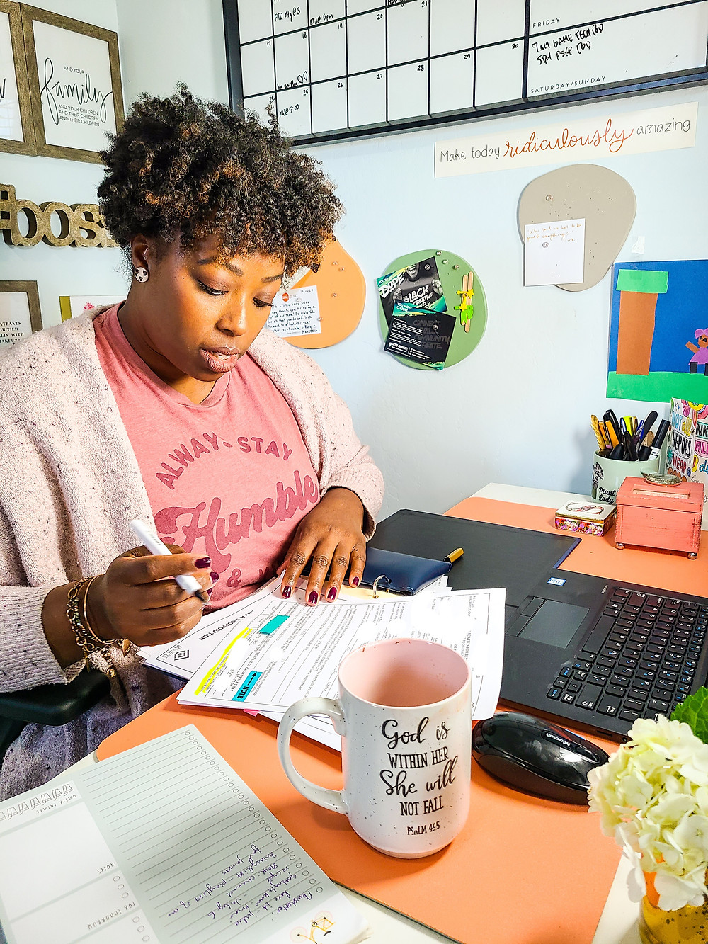 "Black woman holding pen and signing legal documents, while sitting at desk. Desk topped with flowers, coffee cup, to-do list and pen, cup of pens. Walls decorated with calendar and art. Shanell Tyus. Naturalista with curly tapered haircut. Two-strand twists. Pink graphic tee that says ""Always Stay Humble"". Light-purple cardigan sweater."
