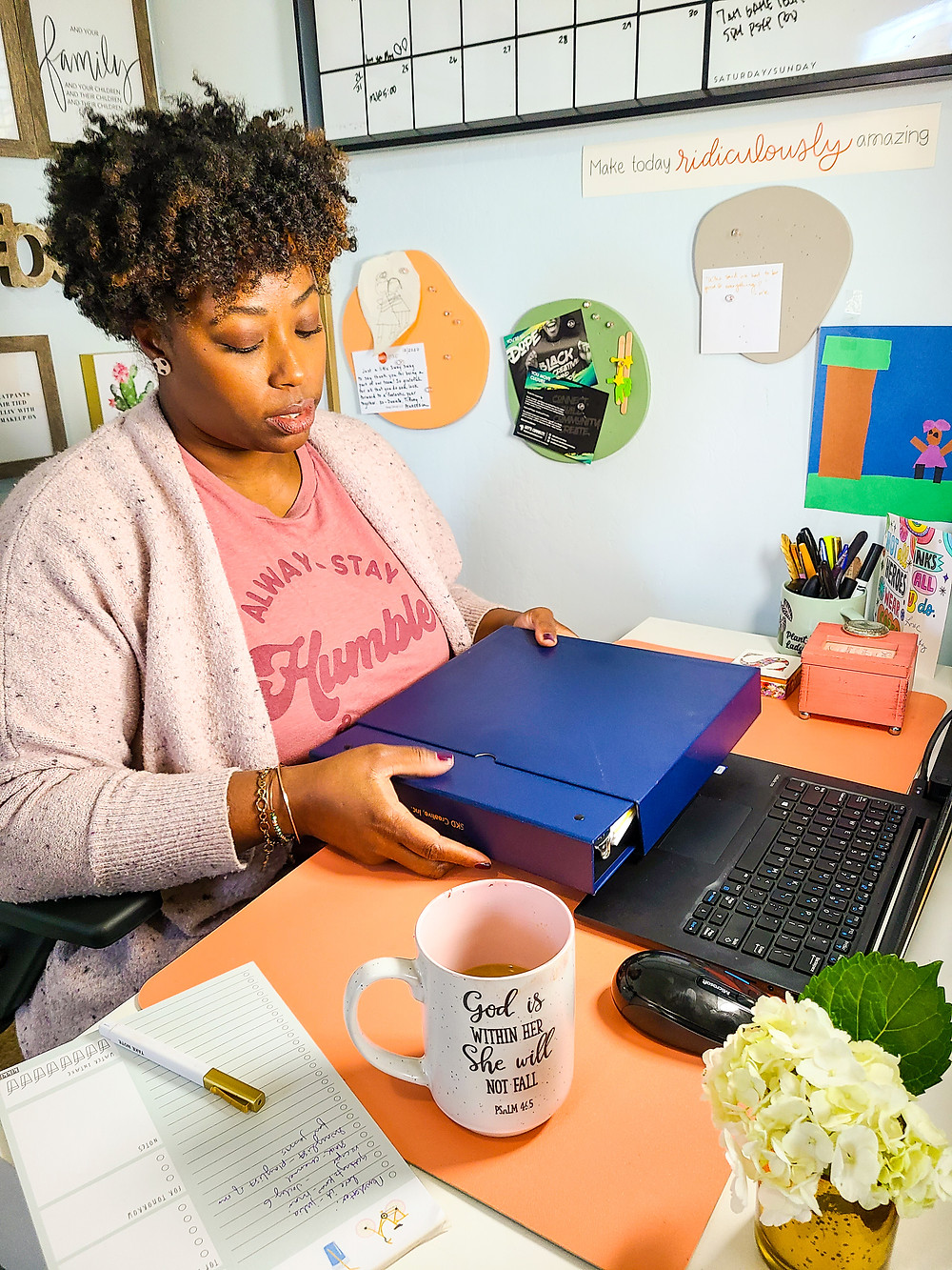 "Black woman holding business binder, while sitting at desk. Desk topped with flowers, coffee cup, to-do list and pen, cup of pens. Walls decorated with calendar and art. Shanell Tyus. Naturalista with curly tapered haircut. Two-strand twists. Pink graphic tee that says ""Always Stay Humble"". Light-purple cardigan sweater."