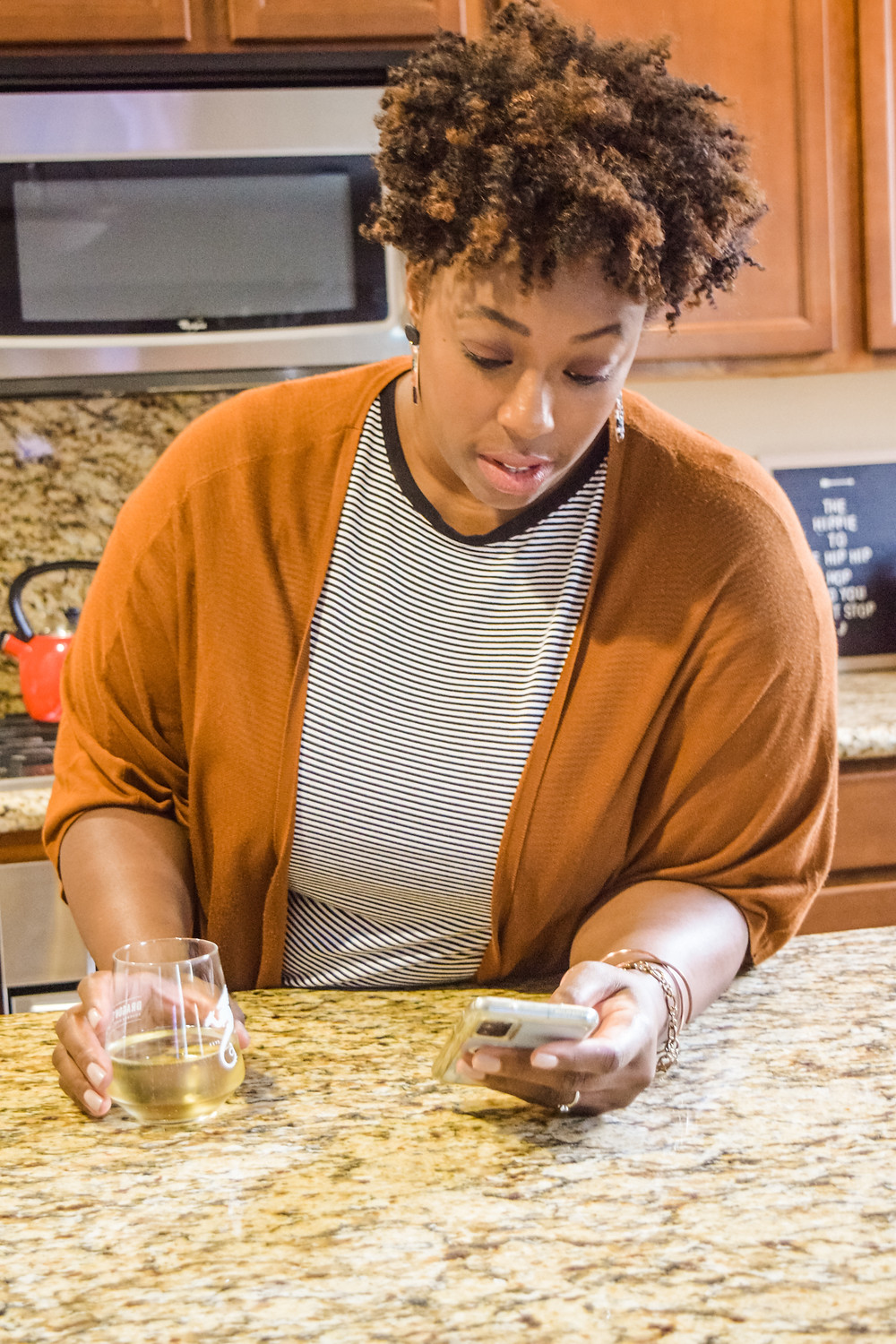 Shanell Tyus Black Mom on her phone with a glass of wine in the kitchen