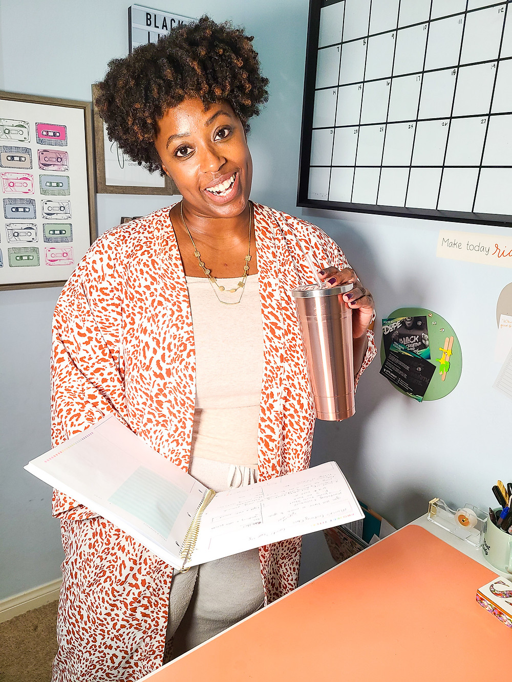 Working in home office. Shanell Tyus. Black xennial mom. Millennial mom. Naturalista. Curly-haired mom. Tapered cut. Cozy home office. Work from home mom. Mompreneur. Finding your passion. Black woman standing in from of desk smily while holding a tumbler cup in left hand and an open planner in her right hand. Curly hair and taperd cut, ivory colored shirt and pants, gold necklace, and white and orange printed kimono. Black mompreneur.