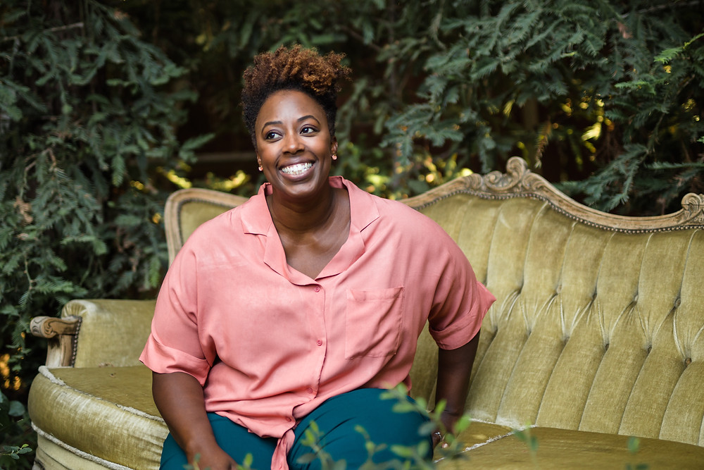 African American woman, sitting on green velvet victorian style couch outdoors in front of greenery. Wearing coral colored shirt, dark teal pants, natrual curly tappered hair cut, smiling. Black mompreneur blogger.