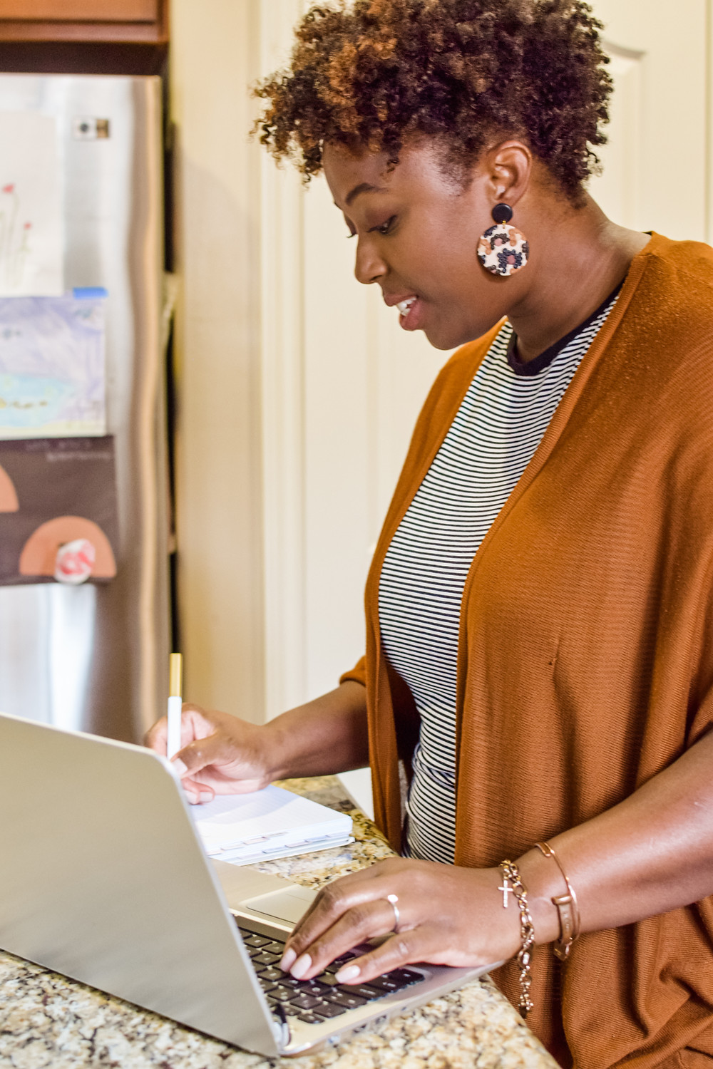 Shanell Tyus Black Mom on the computer working from home writing in planner while standing in the kitchen. Curly haired Black mom with tapered cut.