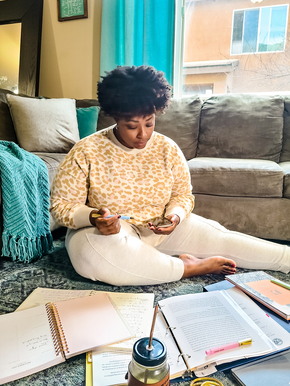 African American woman sitting on floor, surrounded by journals and planners. Planning and strategy help optimize business. Shanell Tyus. Curly hair. Taper cut. Leopard print. Cozy at home. Cozy home shot. Planning and strategizing.