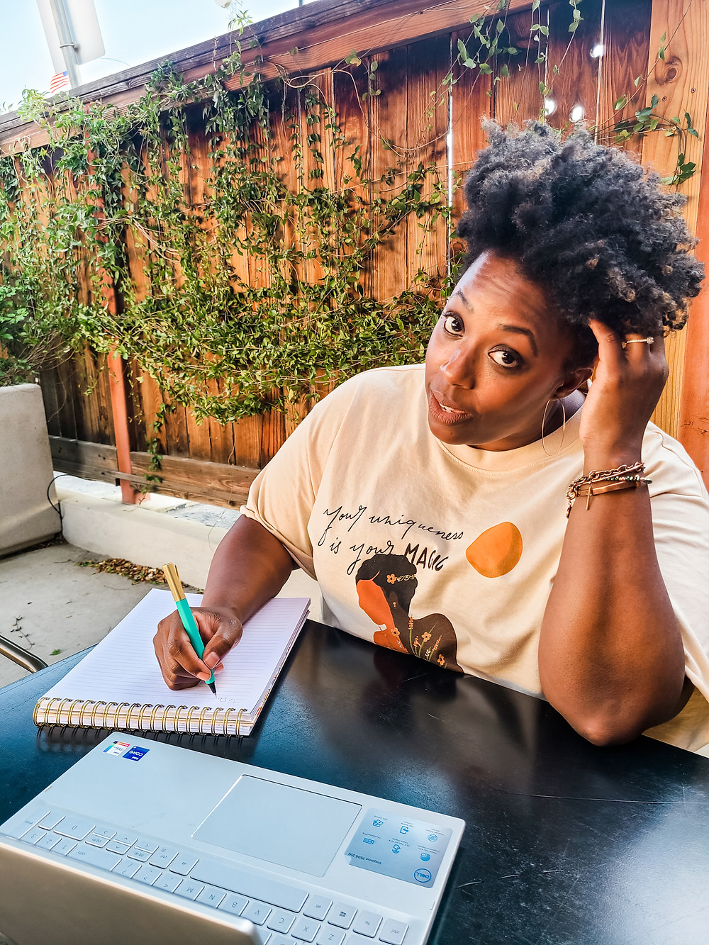 African American woman sitting outdoors at a table, writing on a spiral notebook with a teal colored pen in right hand, adn an open laptop in front. Left hand is bent up and fingers inside of her curly tapered haircut. Ivory colored shirt with an African American woman on the front, and illegible black writing. Head tilted up towards camera, making direct eye contact. Wooden fence with green vines behind her. Shanell Tyus. Black Blogger.