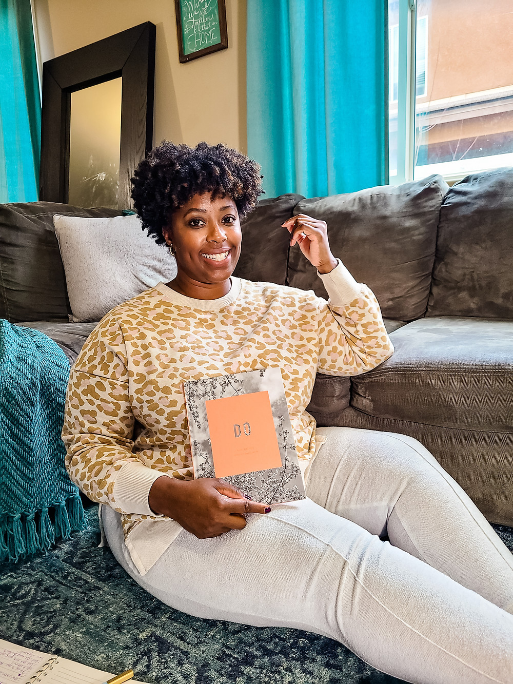 African American woman sitting on floor, holding journal. Shanell Tyus. Curly hair. Taper cut. Leopard print. Cozy at home. Cozy home shot. Planning and strategizing.