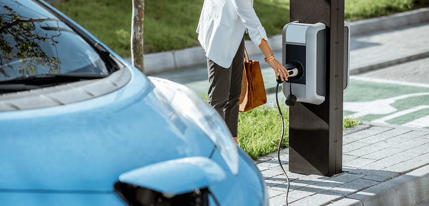 woman charging electric vehicle