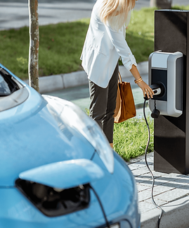 Woman charging electric vehicle with public ev charger