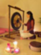 Zittende dame bespeelt de gong. Om haar heen zijn zitkussens gedrapeerd en op de voorgrond branden kaarsen.