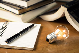 Desk with notepad and pen, books and an illuminated light bulb