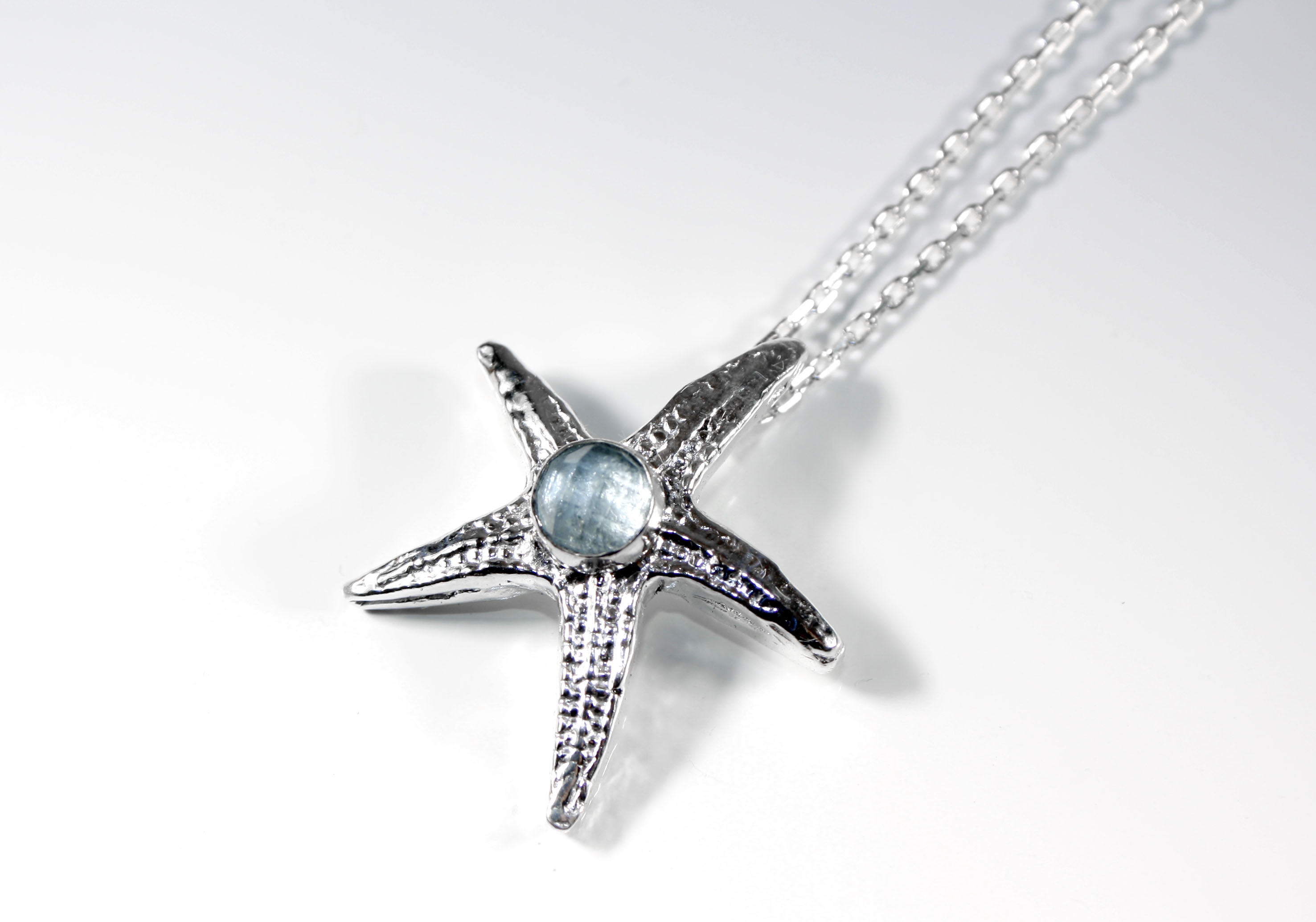 Starfish pendant with faceted aquamarine lying close up