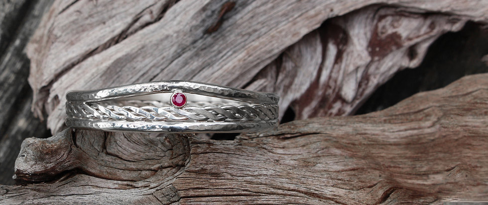 Twist weave centre bangle with ruby on wood - colour.jpg