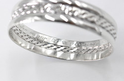 Wide sterling silver bangle with a woven centre and engraved message close up of engraving