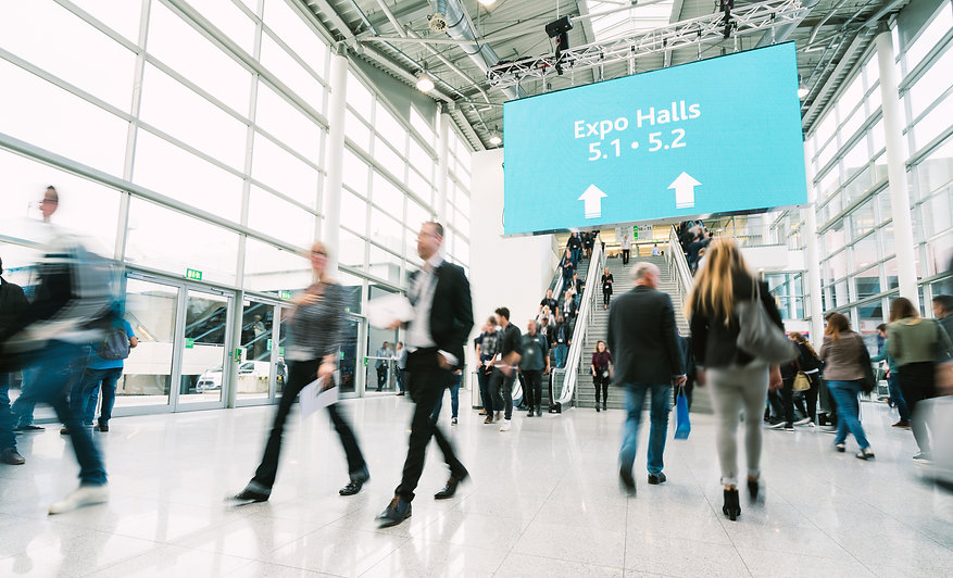 People walking in an exhibition centre with stairs and escalator in background