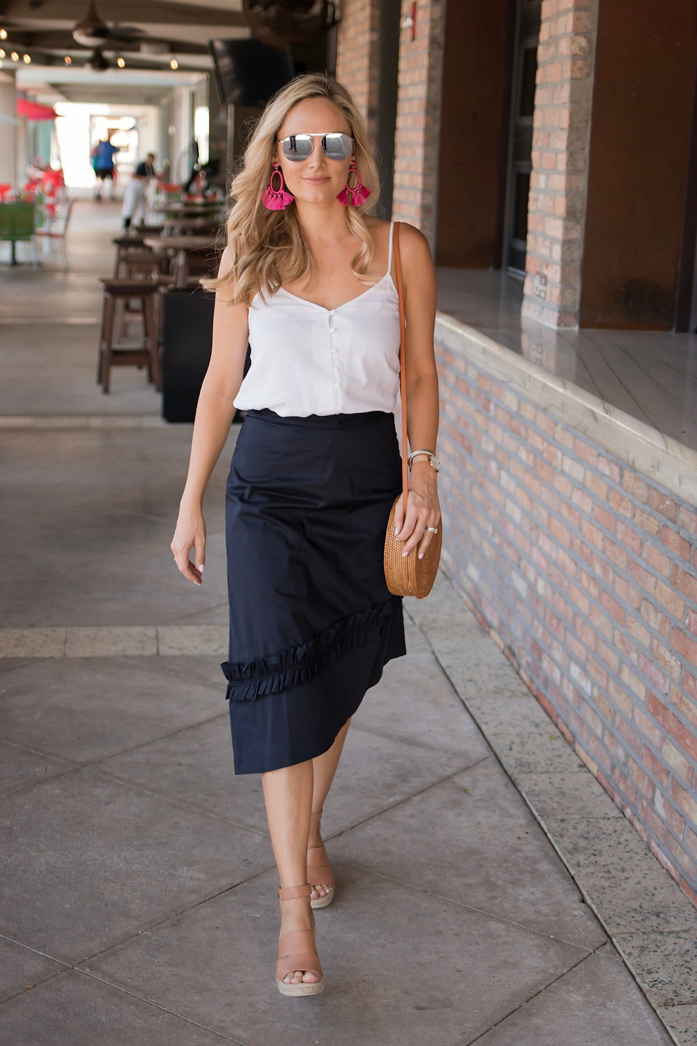 girl walking wearing navy ruffled Ivanka trump asymmetrical hem skirt with white linen cami top with straw circular bag