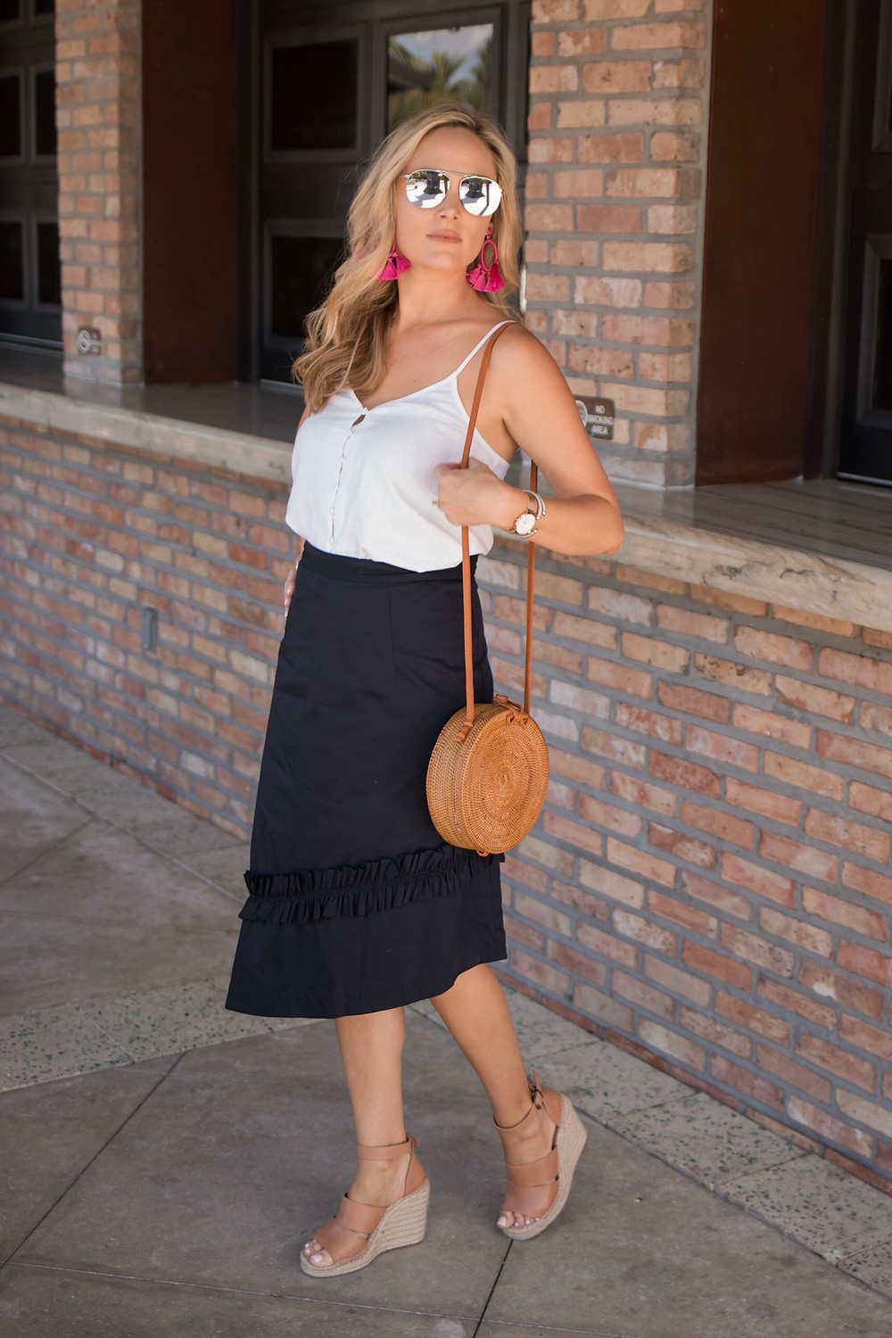 girl wearing navy ruffled Ivanka trump asymmetrical hem skirt with white linen cami top with straw circular bag