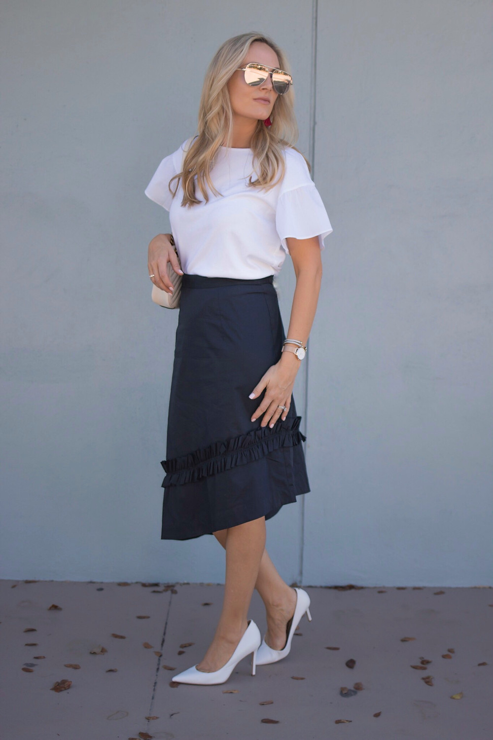 girl wearing navy ruffled Ivanka trump asymmetrical hem skirt with white ruffled top