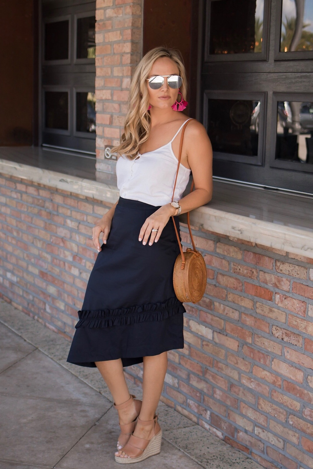 girl wearing navy ruffled Ivanka trump asymmetrical hem skirt with white linen cami top