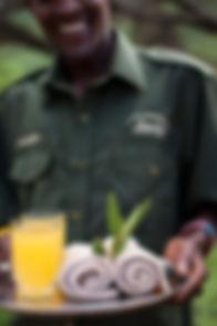 Welcome to Koros Camp. Maasai man with drinks