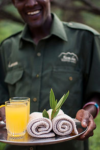 Welcome to Koros Camp. Maasai man with drinks