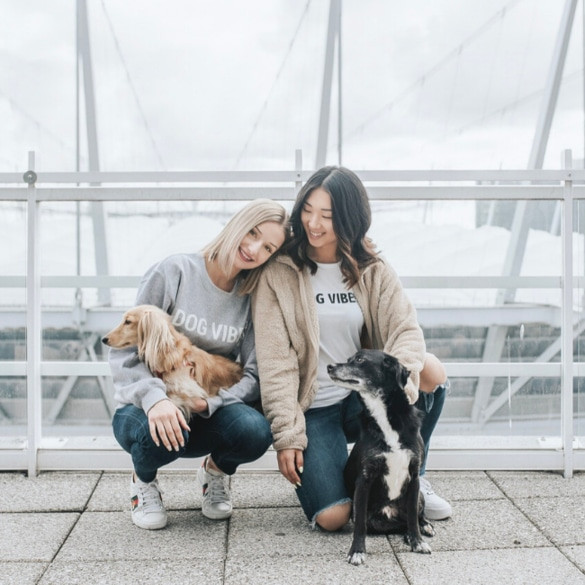 Two girls wearing PawSwap clothes and their dogs