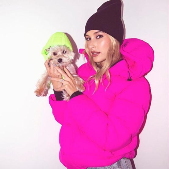 Girl holding a cute dog wearing an Aritzia's dog hat