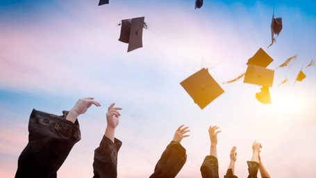 graduates throwing graduation hats in th