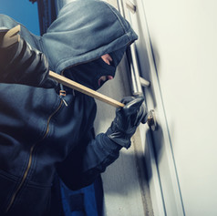 masked burglar opens a door with a crowb