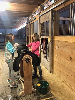 Violet and Sophia cleaning saddle.jpg