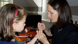 Student learning violin in private lesson
