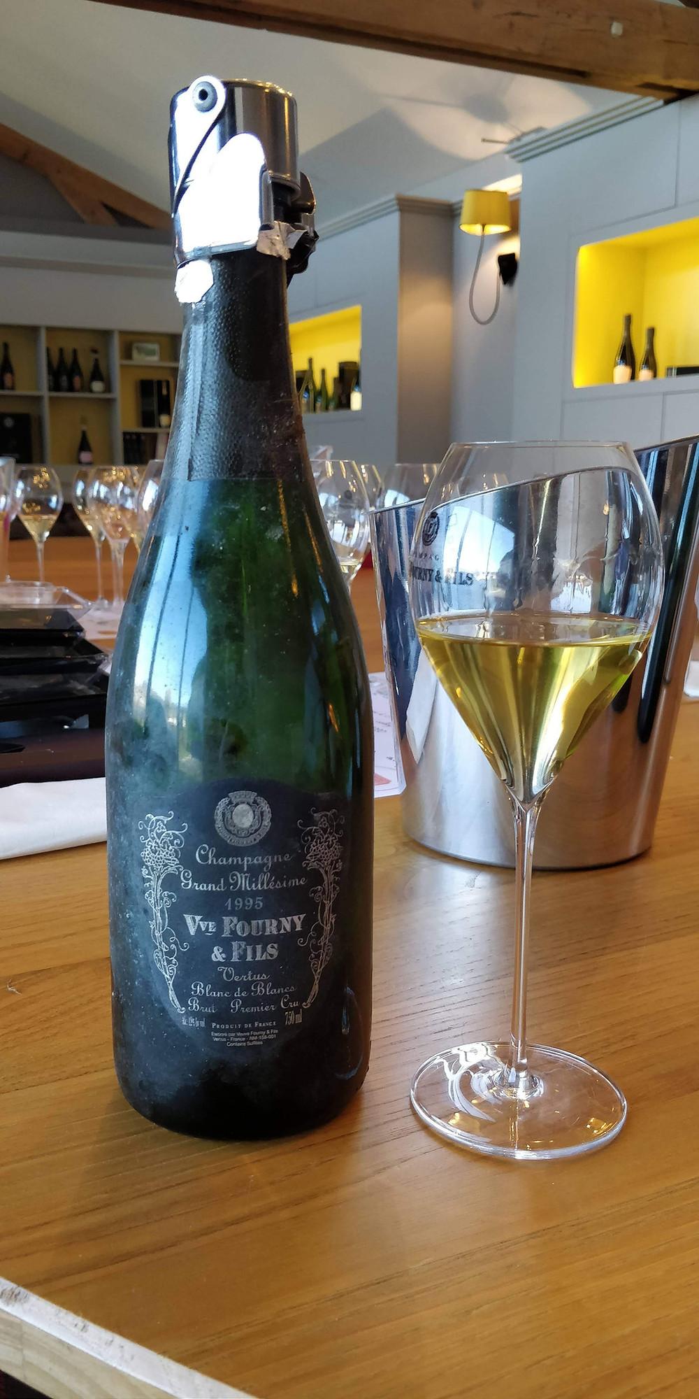 Bouteille de champagne posée sur la table avec un verre rempli