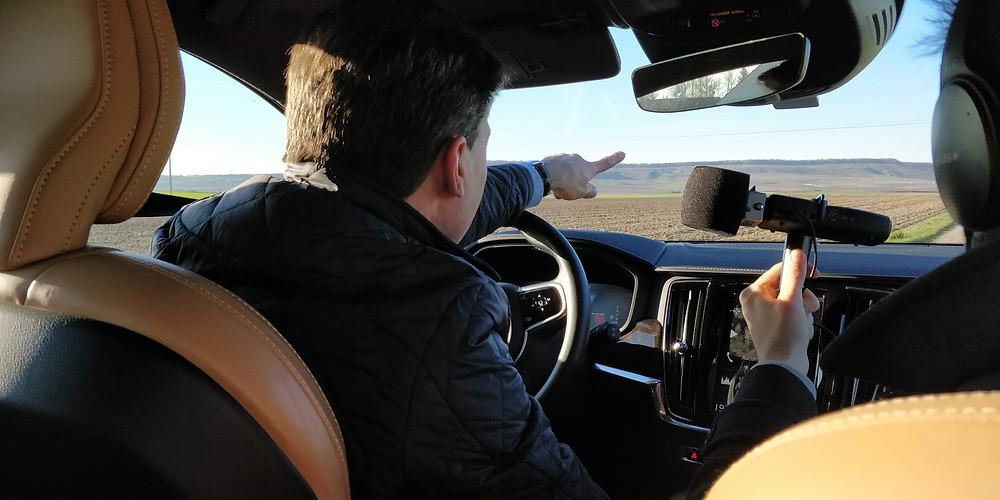 Assis dans sa voiture, le vigneron Charles-Henry montre les paysages de le Champagne en répondant au micro.