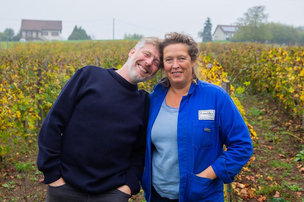 Le couple d'associés du domaine Les Bottes Rouges devant des pieds de vigne dans le Jura
