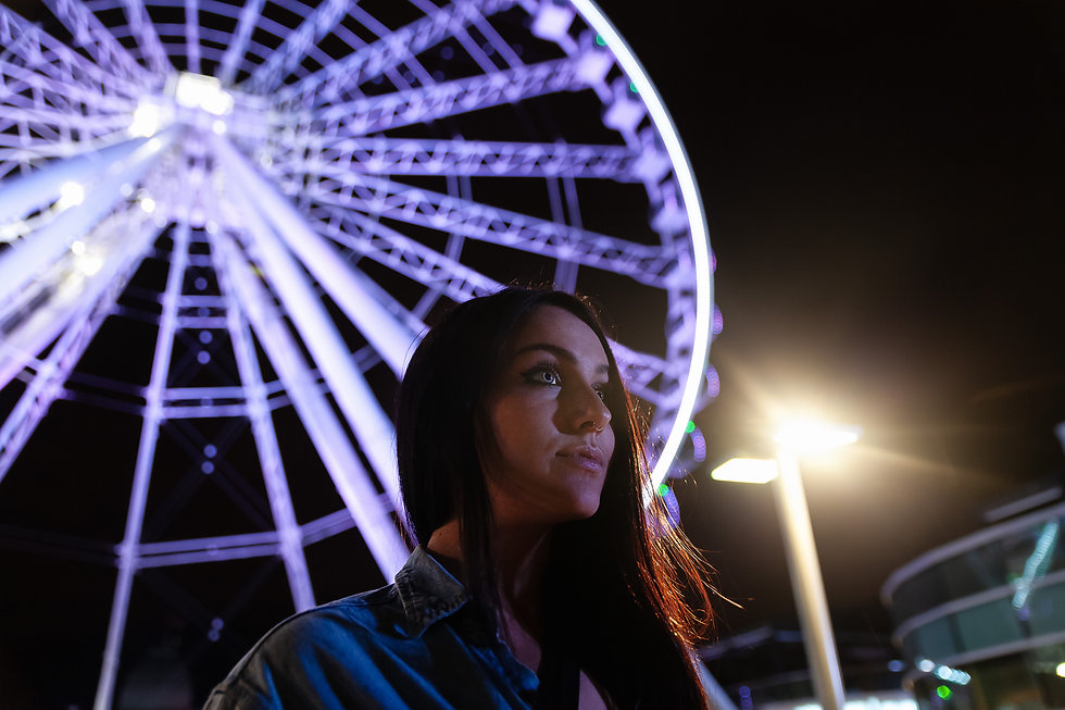 Portrait d'un femme aux yeux bleus de nuit devant la grande roue de Montréal
