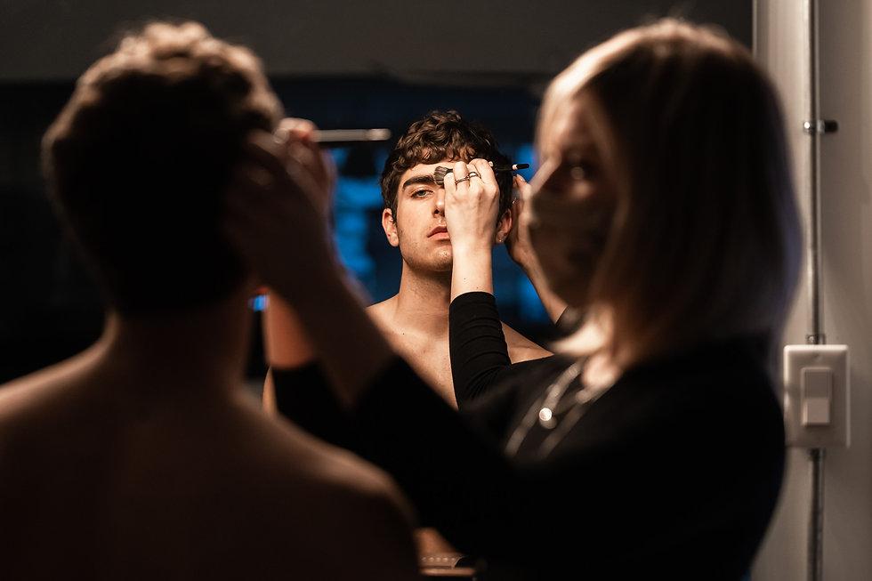 Une maquilleuse MUA maquillant un modèle avec reflet dans le miroir