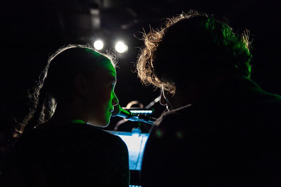 Regard complice entre une élève et sa professeur de musique, jouant sur scène avec Jeunes Musiciens du Monde