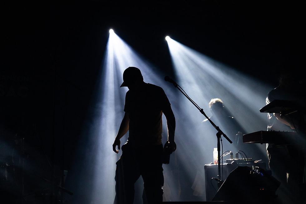 Chanteur en silhouette lors de l'entrée du groupe Loco Locass sur scène pour le concert d'ouverture du Festival de la Chanson de Tadoussac